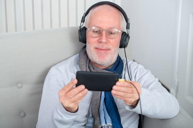 Homem sênior em fones de ouvido, ouvindo música em casa
