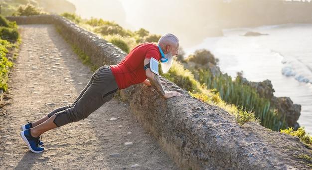 Homem sênior em forma se alongando ao ar livre ao pôr do sol antes da sessão de treino