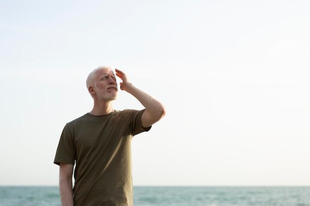 Homem sênior em foto média posando à beira-mar