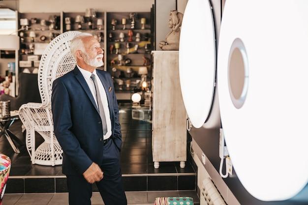 Homem sênior em loja de iluminação doméstica fotografando o shandelier para sua casa