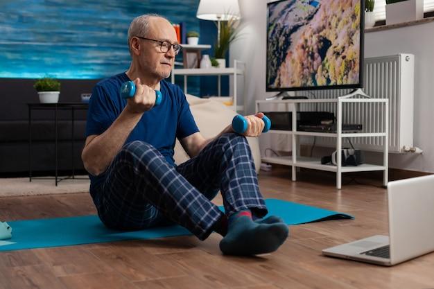 Homem sênior em roupas esportivas aquecendo os músculos do corpo praticando exercícios de bem-estar