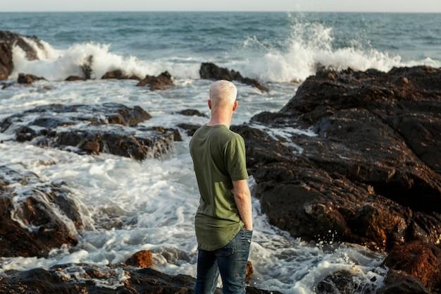 Homem sênior em tiro médio à beira-mar