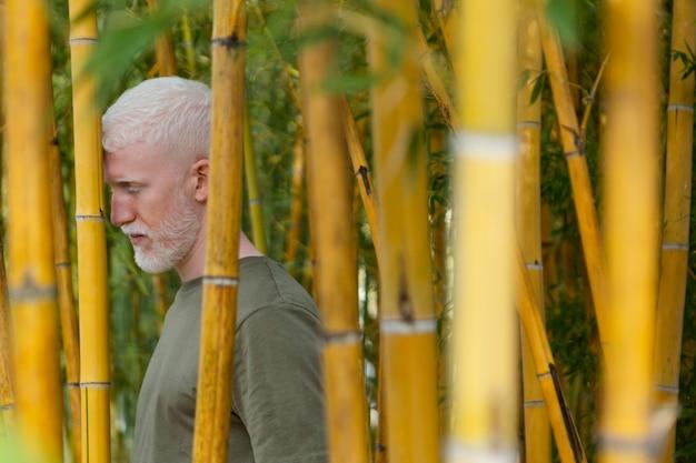 Homem sênior em tiro médio posando com bambu