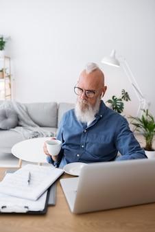 Homem sênior em tiro médio segurando uma xícara de café
