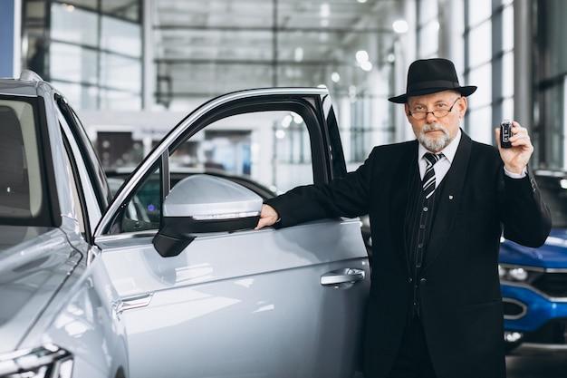 Homem sênior em um showroom de carro, escolhendo um carro