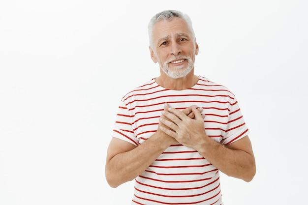 Homem sênior emocionado e feliz, lisonjeado de mãos dadas no coração e sorrindo