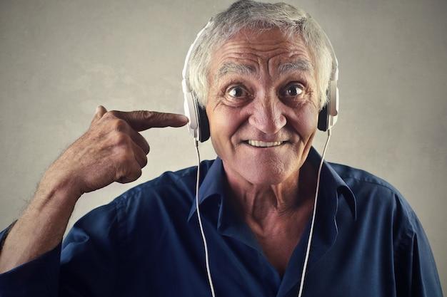 Homem sênior, escutar música, ligado, fones