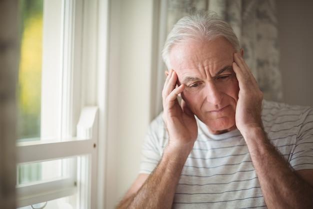 Homem sênior estressado parado perto da janela