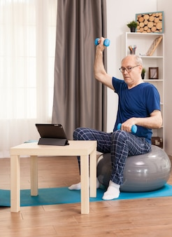 Homem sênior fazendo exercícios de recuperação muscular sentado em uma bola suíça em frente ao tablet