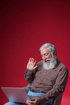 Homem sênior feliz acenando sua mão enquanto vídeo conversando no laptop contra o pano de fundo vermelho