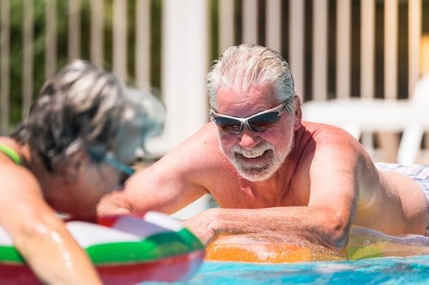 Homem sênior feliz alegre e sorridente curtindo a piscina de verão em casal se aposentou.