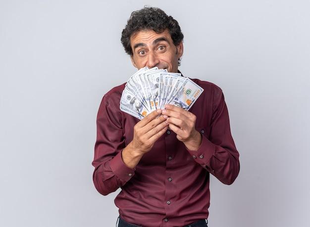 Homem sênior feliz e animado com camisa roxa segurando dinheiro olhando para a câmera surpreso em pé sobre o branco