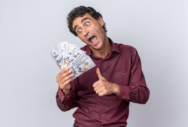 Homem sênior feliz e animado de camisa roxa segurando dinheiro, olhando para o dinheiro, sorrindo alegremente, mostrando os polegares em pé sobre um fundo branco