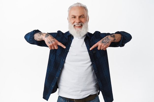 Homem sênior feliz e sorridente com barba e tatuagens, apontando o dedo para o centro, mostrando o banner do seu logotipo, demonstrando o lugar para propaganda, em pé sobre a parede branca