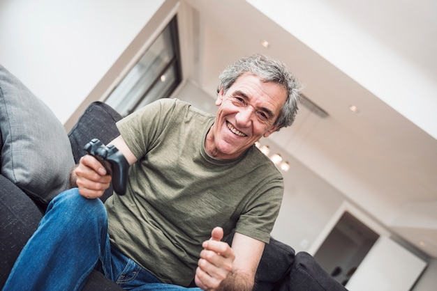 Homem sênior feliz jogando videogame em casa