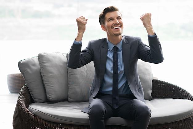 Homem sênior feliz que levanta os braços ao sentar-se no café