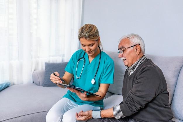 Homem sênior feliz que tem sua pressão sanguínea medida em um lar de idosos por seu cuidador.
