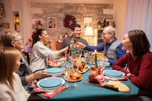 Homem sênior feliz tilintando uma taça de vinho com a filha no jantar de natal em família.