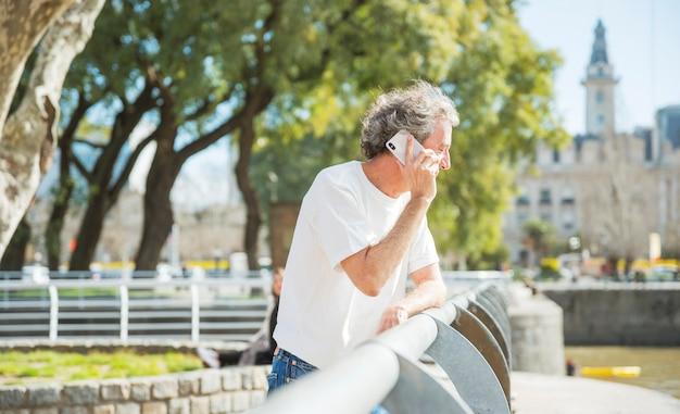 Homem sênior, ficar, perto, a, trilhos, falando telefone móvel, parque