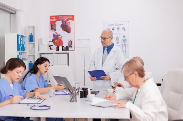 Homem sênior fisioterapeuta discutindo o exame de doença com a equipe médica, analisando os sintomas da doença, apresentando tratamento de saúde. médicos praticantes trabalhando na sala de conferências