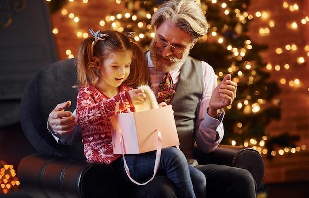 Homem sênior formado alegre com cabelos grisalhos e barba com uma menina com caixa de presente.