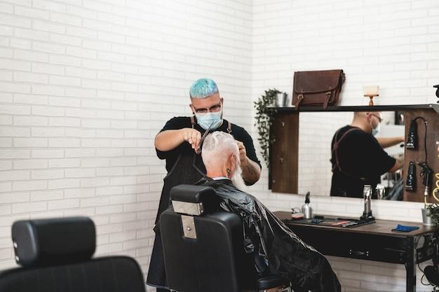 Homem sênior hippie cortando cabelo em uma barbearia vintage
