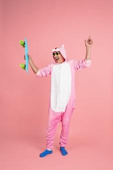 Homem sênior hippie em traje rosa elegante, isolado no fundo rosa. tecnologia e alegria