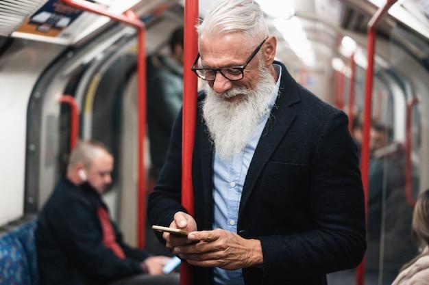 Homem sênior hippie feliz assistindo smartphone no metrô. foco no rosto