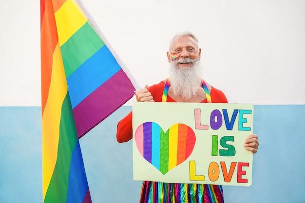Homem sênior hippie no orgulho gay segurando a bandeira do arco-íris e a bandeira lgbt - foco no rosto