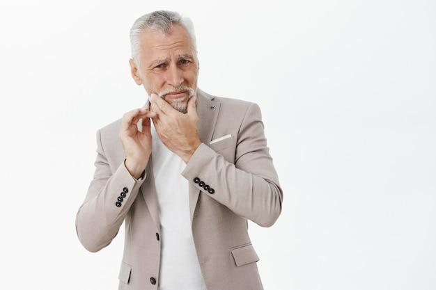 Homem sênior incomodado com jaqueta tocando o queixo e reclamando de dor de dente