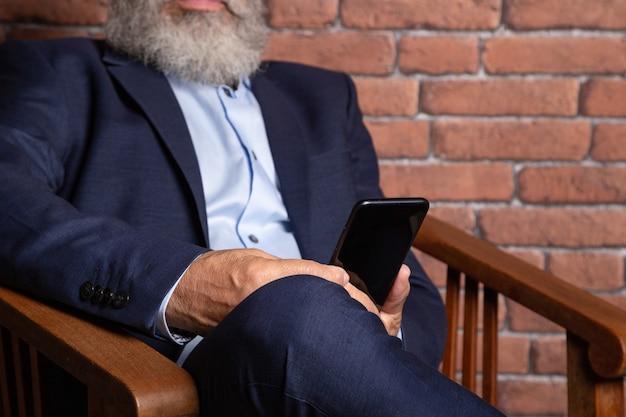 Homem sênior irreconhecível de terno e barba branca, consultar o aplicativo no telefone no escritório, foto das mãos de um homem usando o smartphone nas costas de um empresário.