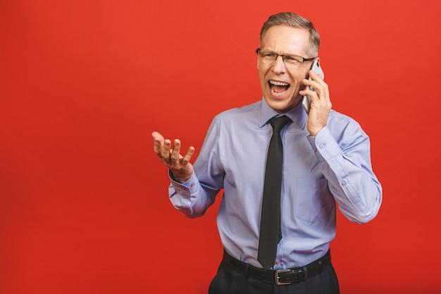 Homem sênior irritado que fala no telefone móvel isolado na parede vermelha. emoções negativas.