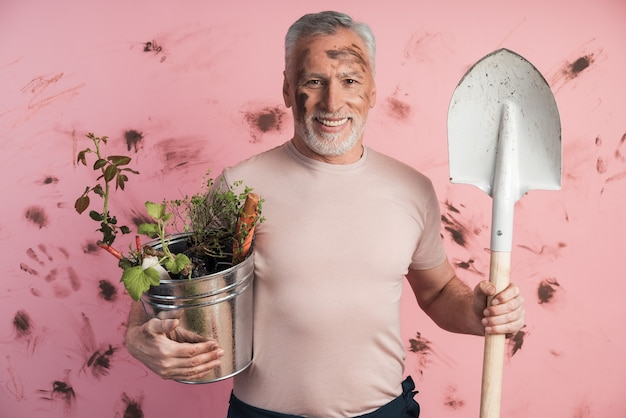 Homem sênior, jardineiro com uma pá e um balde nas mãos