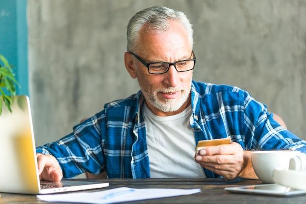 Homem sênior, leitura, crédito, cartão, número, enquanto, trabalhando, laptop
