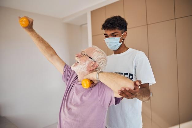 Homem sênior levantando peso apoiado por um instrutor