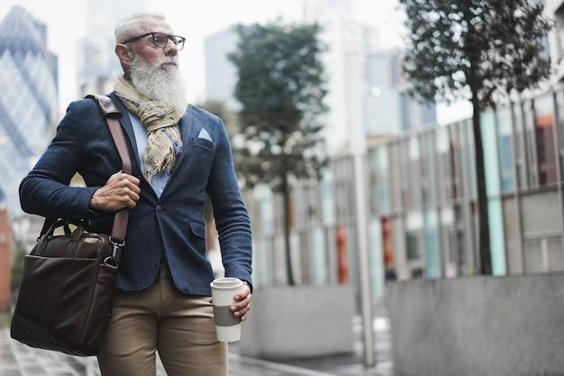 Homem sênior moderno de negócios em pé confiante enquanto bebe café num dia de inverno - foco no rosto