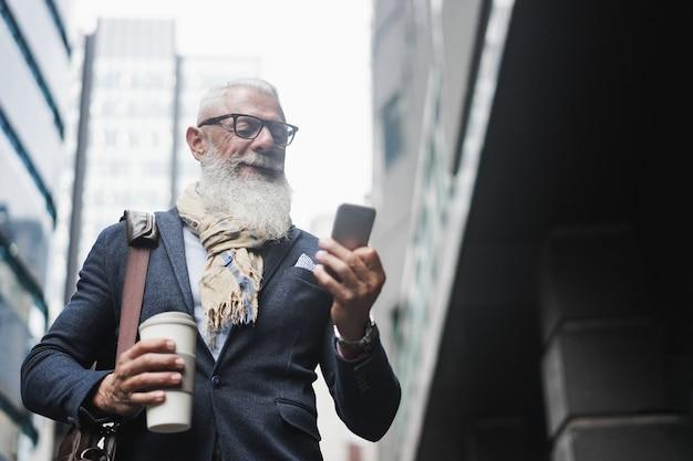 Homem sênior moderno de negócios usando telefone celular e bebendo café na cidade
