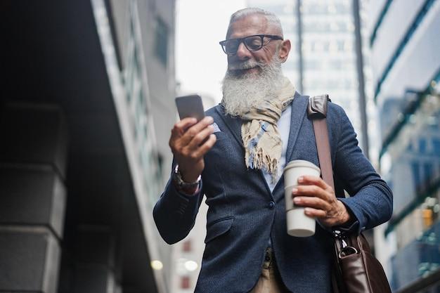 Homem sênior moderno de negócios usando telefone celular enquanto caminha para trabalhar com edifícios no fundo - rosto de foco