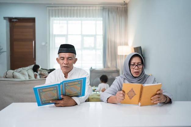 Homem sênior muçulmano asiático ensinando a esposa a ler o alcorão ou o alcorão na sala de estar. casal muçulmano rezando em casa