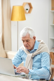Homem sênior muito ocupado com suor nos ombros usando laptop enquanto navega na internet em casa