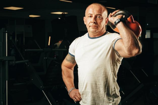 Homem sênior na casa dos cinquenta, levantando pesos em uma academia