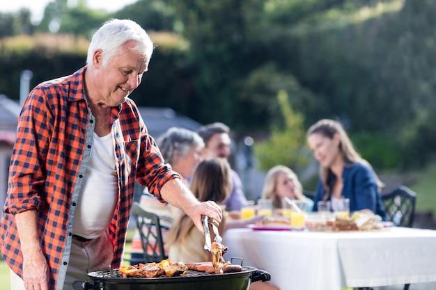Homem sênior na churrasqueira enquanto a família almoçando