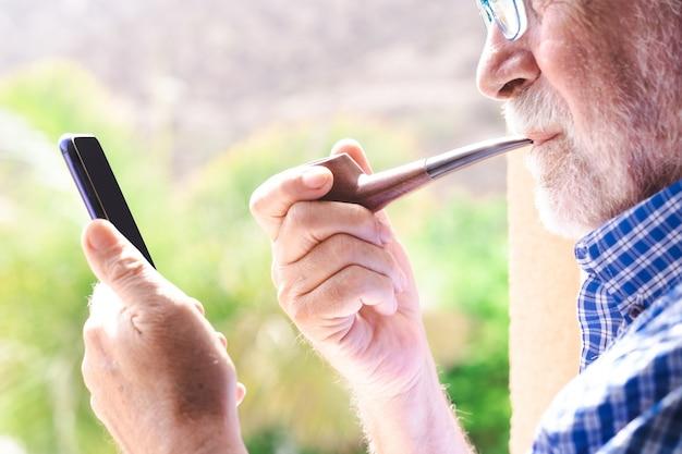 Homem sênior na janela, olhando para o celular, enquanto fuma um cachimbo
