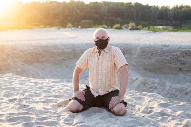 Homem sênior na máscara médica sentado na praia de verão. conceito de quarentena de coronavírus.