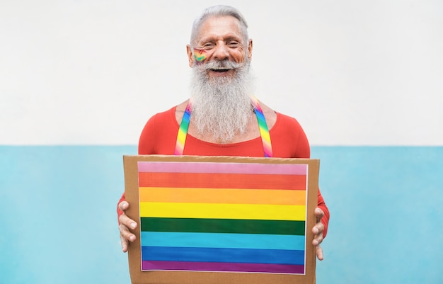 Homem sênior no orgulho gay segurando banner lgbt de arco-íris
