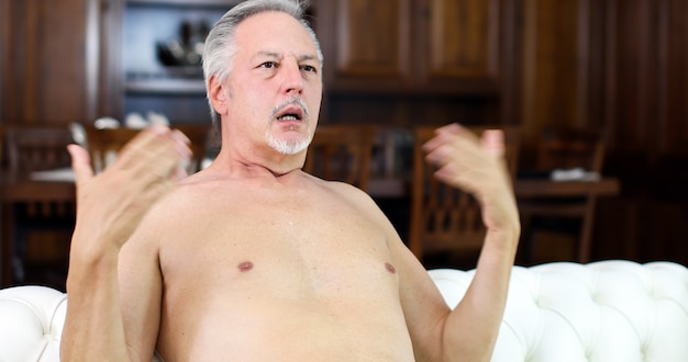 Homem sênior nu, sofrendo pelo calor enquanto está sentado em seu sofá