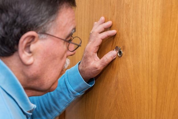 Homem sênior, olhando, peephole