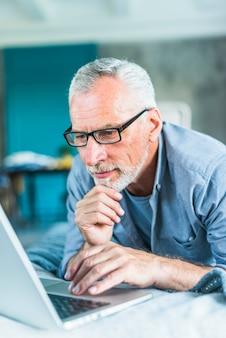 Homem sênior pensativo, navegando no laptop