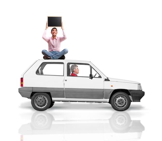 Homem sênior que conduz enquanto outro homem está sentado no teto do carro com um quadro-negro