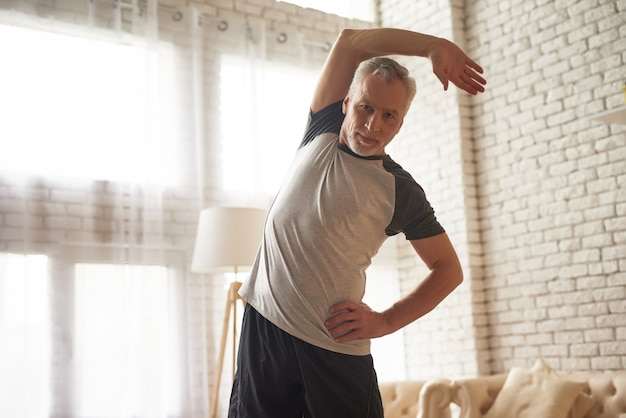 Homem sênior que estica o exercício fácil em casa.
